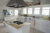 armoires de cuisine blanche, ilôt et hotte de poêle